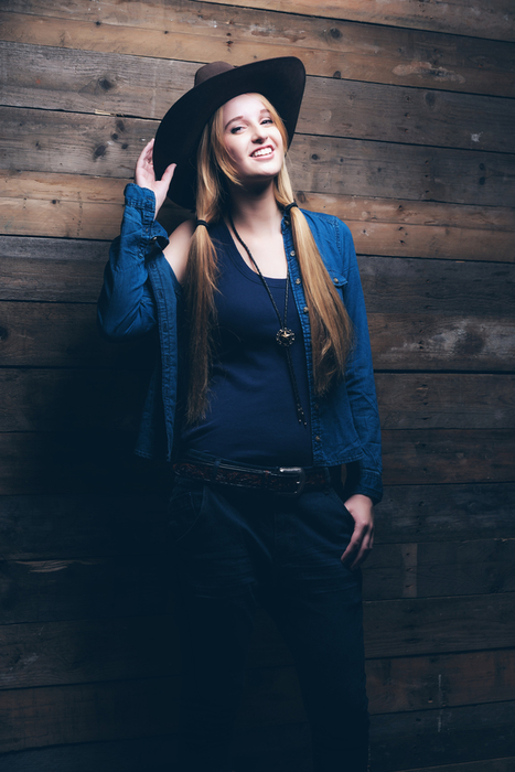 Cowgirl jeans fashion woman with long blonde hair. Standing against wooden wall.