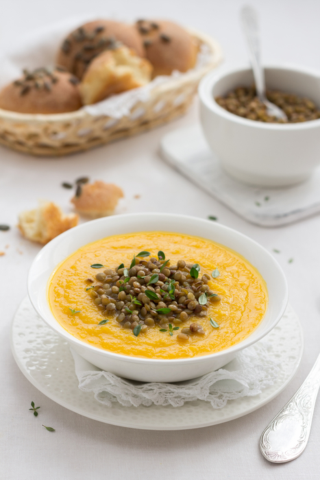 Pumpkin soup with lentils in a white bowl on textiles