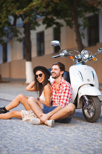 Young couple sitting near white retro scooter