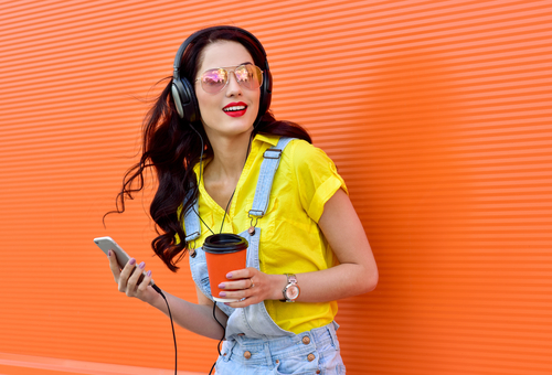 Beautiful smiling woman with headphones listens to music over orange background.  Fashion woman in sunglasses outdoor.