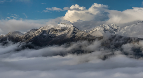 Snow mountain tops in clouds. Dawn. Mount Mamkhurts. Caucasus mountains.