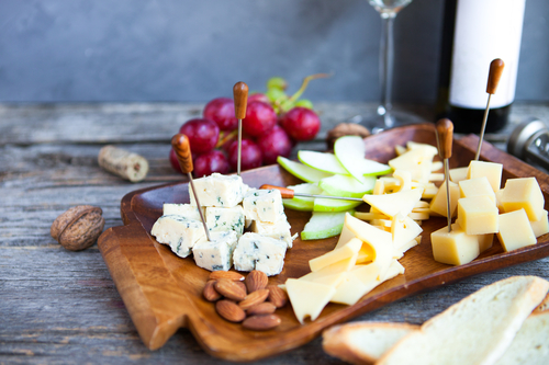Wine snack set. Glass of red and white wine, grape and various sorts cheese, over rustic wooden background.