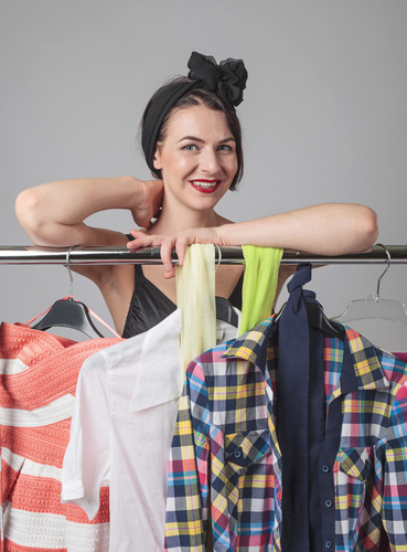 Attractive woman standing near the racks of clothes .