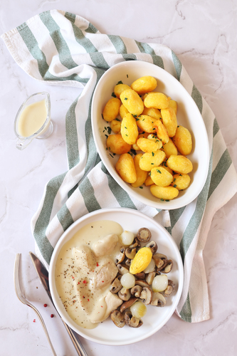 French cuisine. Chicken fricassee with sauce, fried potatoes and mushrooms