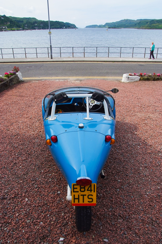 Oban, United Kingdom - February 20, 2010: blackjack avion car on parking at sea quay. Blue automobile with three wheels. Kit car on gravel ground. Transport and transportation. Travel and wanderlust