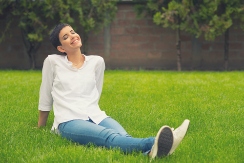 Beautiful smiling girl sitting on the grass of home garden on sunny spring day