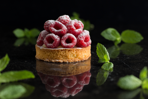 Raspberry tart dessert on dark background. Traditional french sweet pastry. Delicious, appetizing, homemade cake with custard, fresh berries and fruits. Copy space, closeup. Selective focus