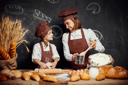 Woman and girl making pastries together